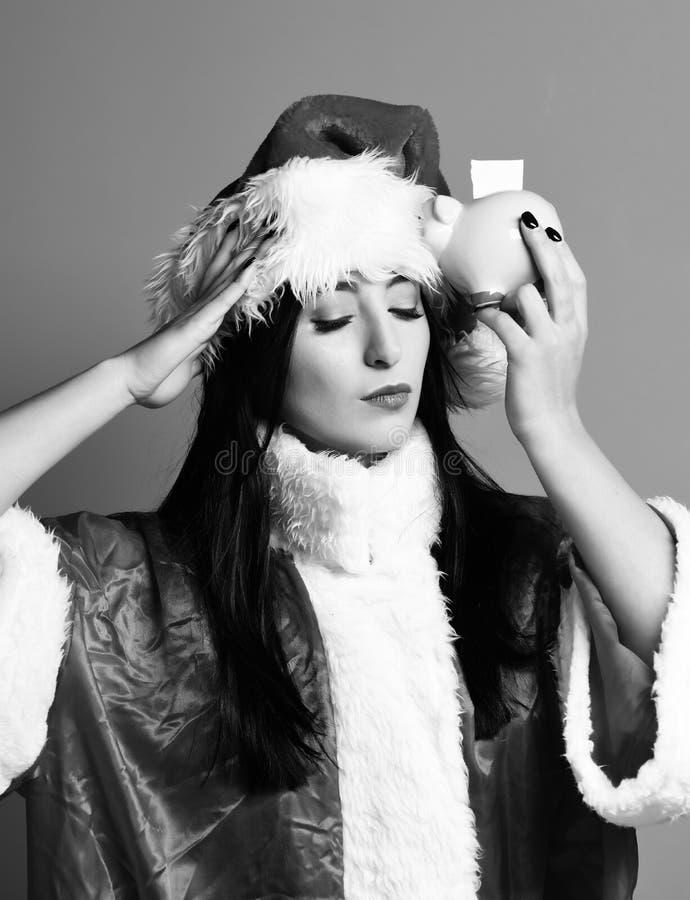 俏丽的逗人喜爱的圣诞老人女孩或深色的妇女有接近的眼睛的在新年毛线衣和圣诞节或者xmas帽子对负桃红色 图库摄影