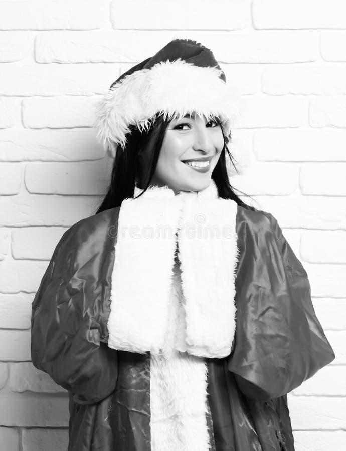 俏丽的逗人喜爱的性感的圣诞老人女孩或微笑的深色的妇女新年红色毛线衣和圣诞节或者xmas帽子的在白色砖 库存图片
