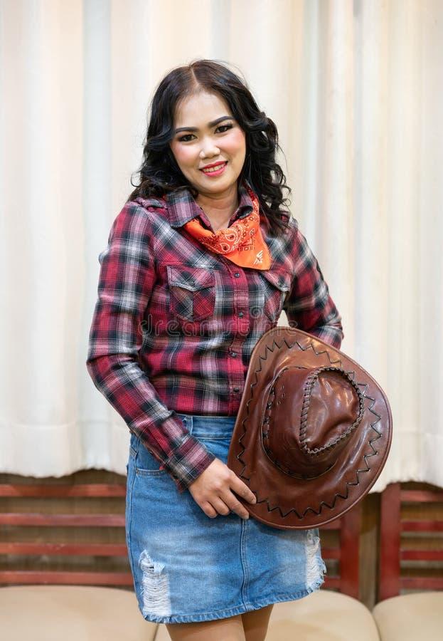 俏丽的长的有牛仔班丹纳花绸的黑色头发亚裔妇女佩带的格子衬衫和在帷幕背景的牛仔帽 免版税库存照片