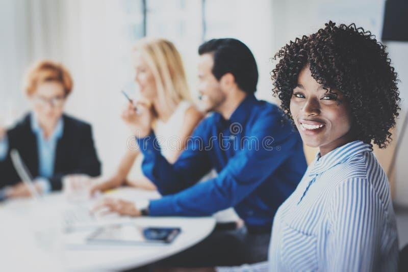俏丽的非裔美国人的女商人画象有非洲微笑的对照相机 在激发灵感的Coworking队 库存照片