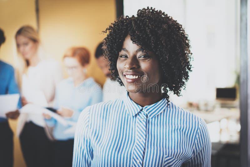 俏丽的非裔美国人的女商人画象有非洲微笑的对照相机 在背景的Coworking队 免版税库存照片