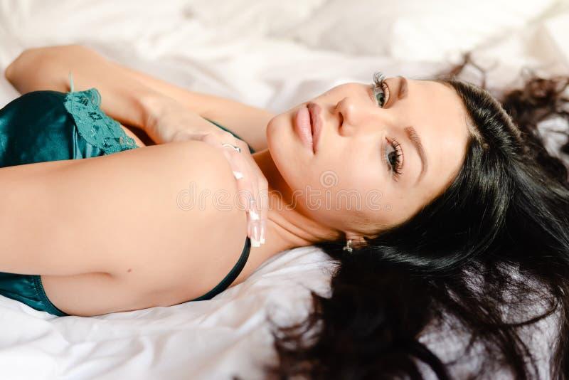 俏丽的绿松石丝绸衬衣的迷人的美丽的妇女&看说谎在白色床背景特写镜头画象的照相机 免版税库存图片
