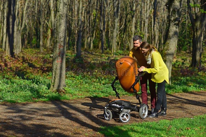 保姆走与婴孩摇篮车在公园 妇女和人保姆照顾小孩 责任和 图库摄影