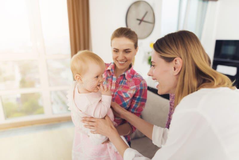 保姆遇见孩子的母亲,抱着她的胳膊的婴孩 更老的女孩拥抱妈妈 库存照片