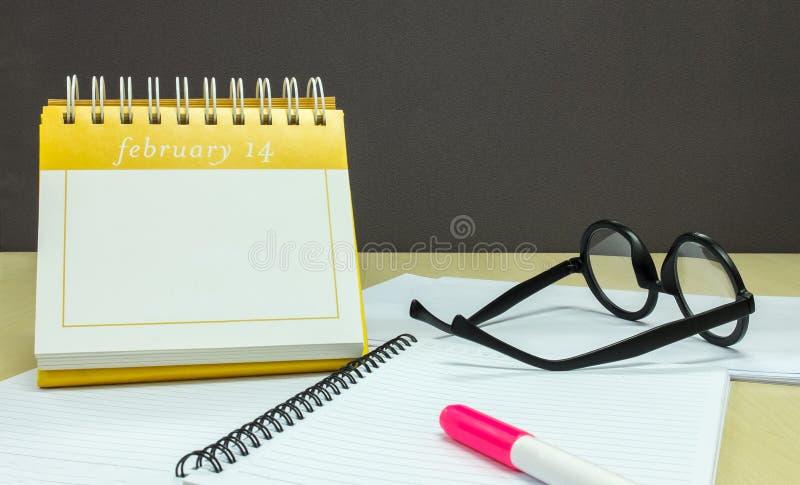 保存您的爱的日期在情人节,日历与桃红色聚焦笔的2月14日,笔记本和玻璃 库存照片