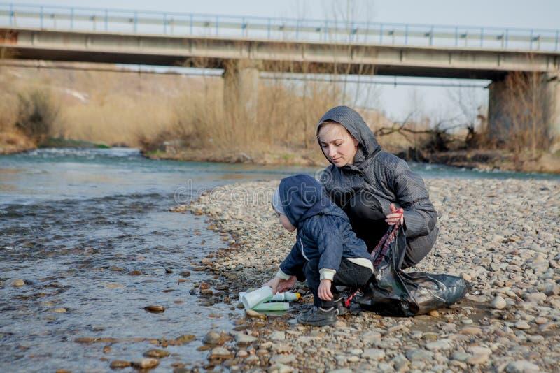 保存环境概念、一个小男孩和他的母亲收集垃圾和塑料瓶在海滩对倾销入 免版税库存图片