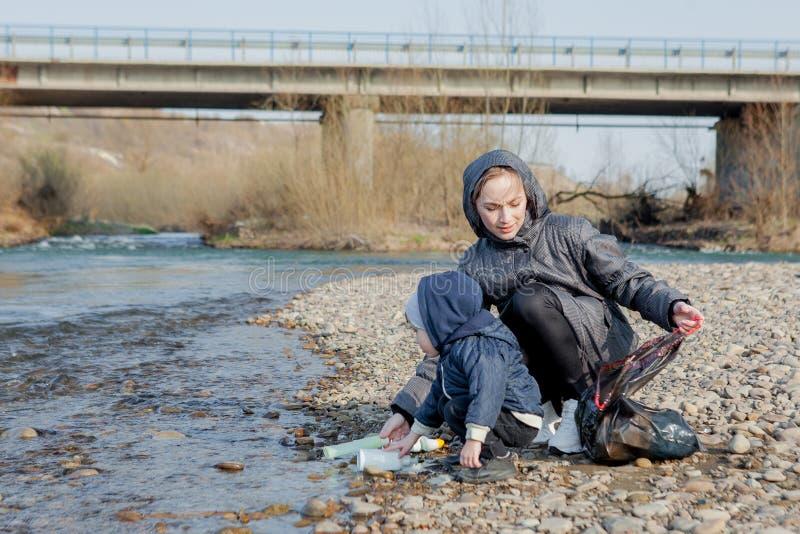 保存环境概念、一个小男孩和他的母亲收集垃圾和塑料瓶在海滩对倾销入 图库摄影