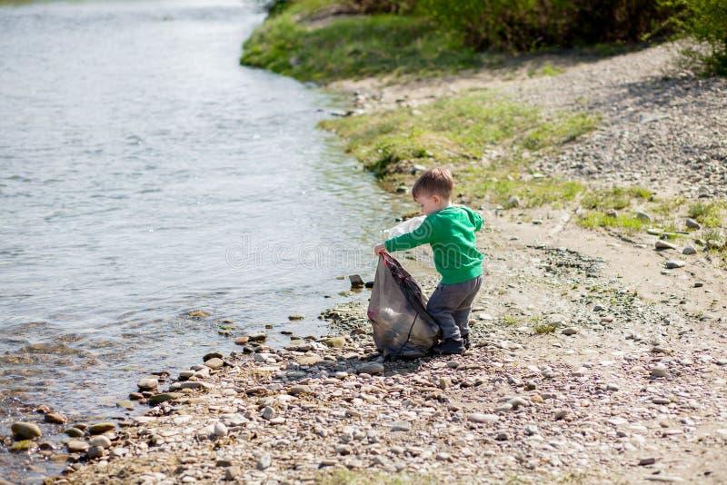 保存环境概念,收集垃圾和塑料瓶在海滩的一个小男孩对倾销入垃圾 库存图片
