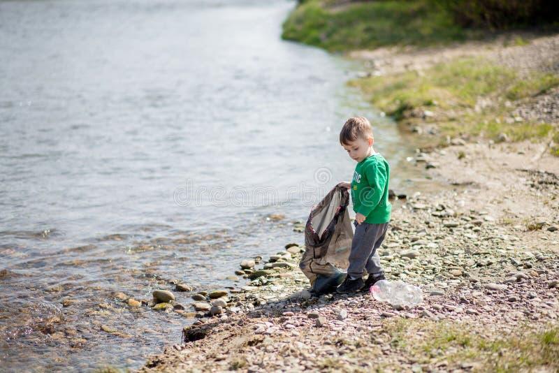 保存环境概念,收集垃圾和塑料瓶在海滩的一个小男孩对倾销入垃圾 图库摄影