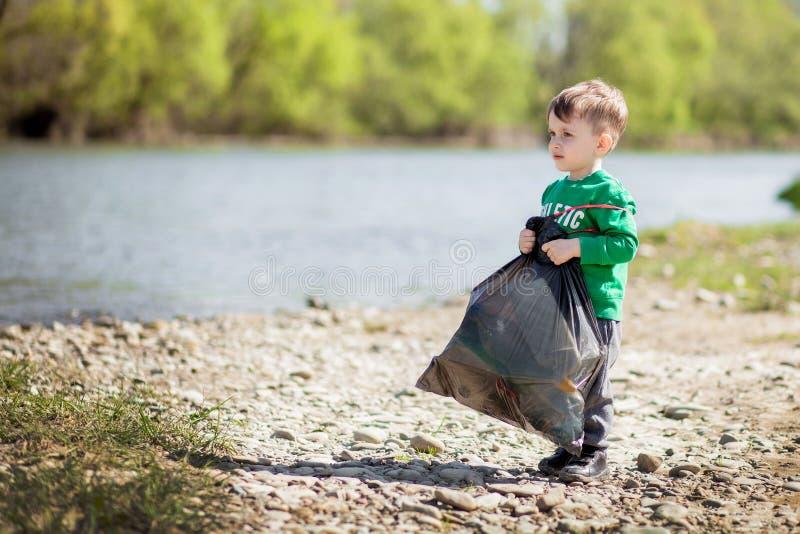 保存环境概念,收集垃圾和塑料瓶在海滩的一个小男孩对倾销入垃圾 免版税库存照片