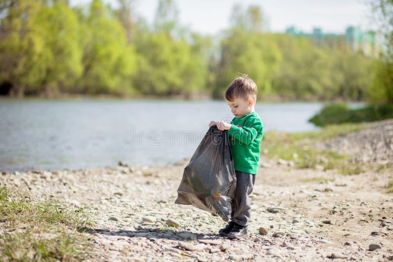 保存环境概念,收集垃圾和塑料瓶在海滩的一个小男孩对倾销入垃圾 库存照片