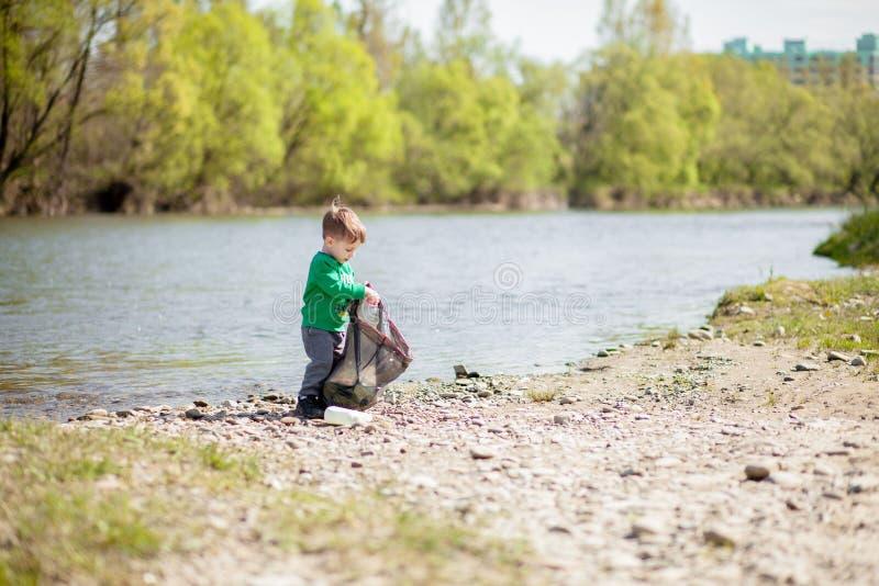 保存环境概念,收集垃圾和塑料瓶在海滩的一个小男孩对倾销入垃圾 免版税图库摄影