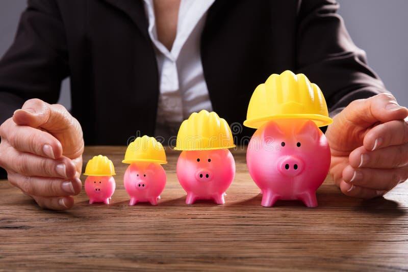保护与黄色安全帽的买卖人Piggybanks 图库摄影