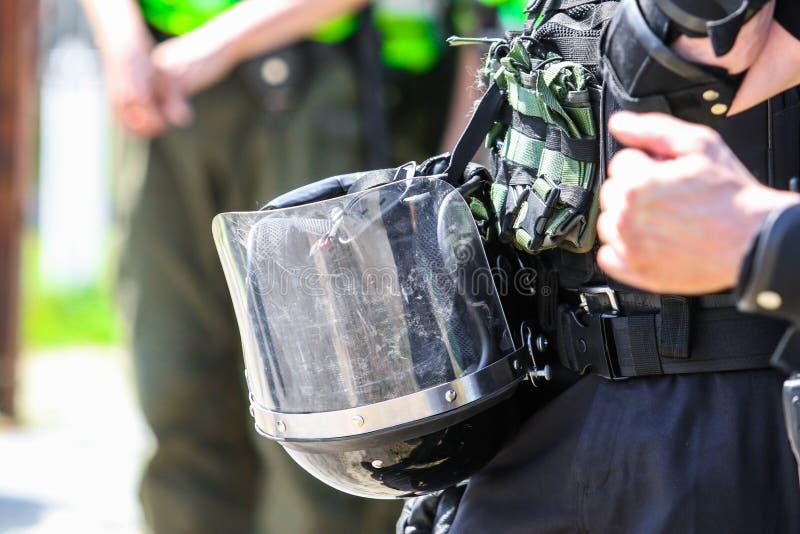 保护他的头的警察的盔甲免受打击 免版税库存照片