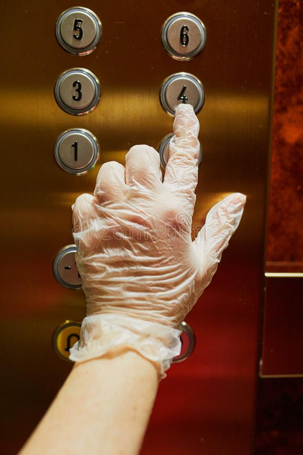 保护性单用手套中的女手按电梯按钮 免版税库存图片