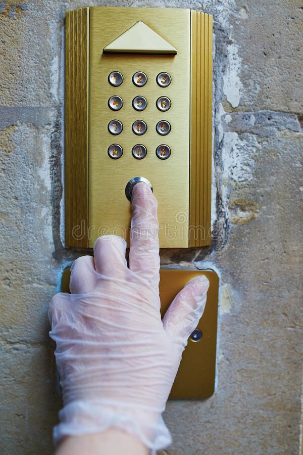 保护性单用手套中的妇女手按住宅的插入按钮 库存图片