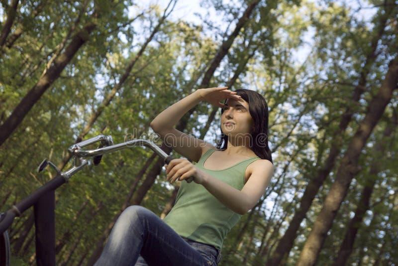保护眼睛的妇女,当骑自行车在森林地时 免版税库存照片