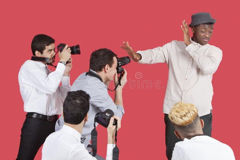 保护从摄影师的幼小公名人面孔在红色背景 免版税图库摄影