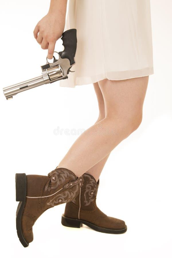 从保持向下使一把大左轮手枪的腰部的女牛仔礼服 库存图片