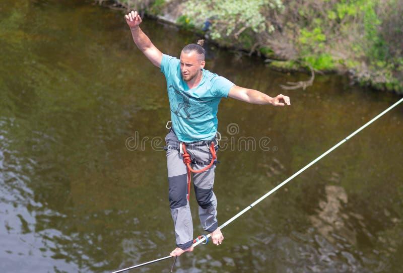 保持在绳索的年轻绳索特技表演者平衡 库存照片