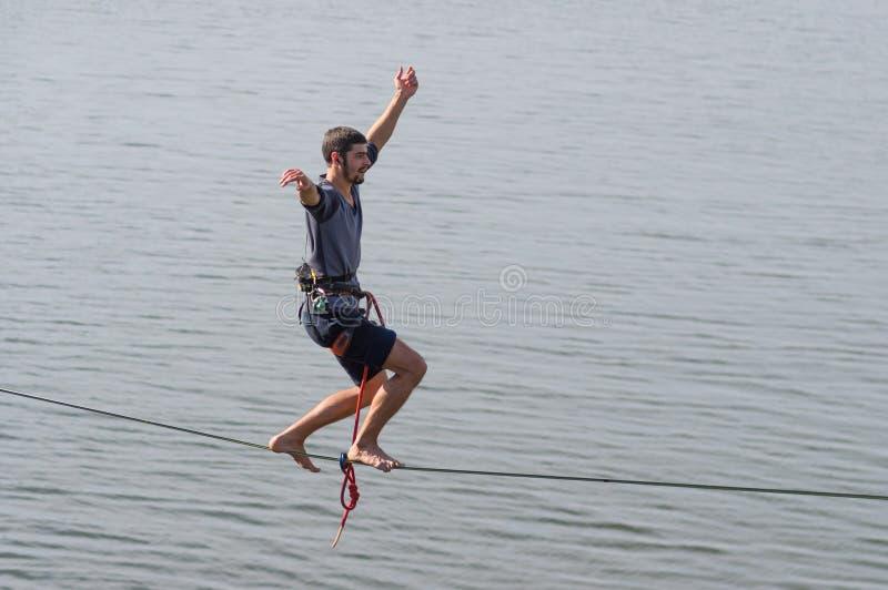 保持在绳索的年轻绳索特技表演者平衡 图库摄影