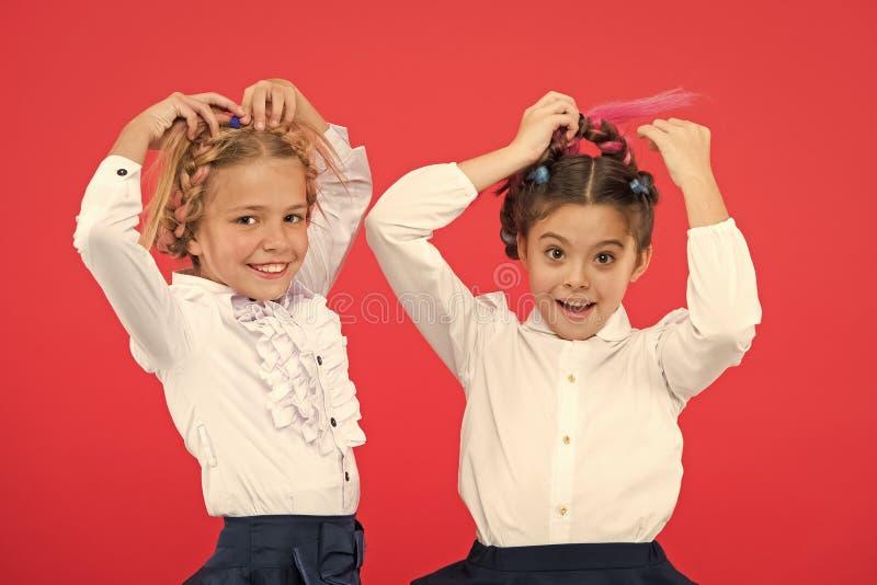 保持头发编辫子为整洁的神色 孩子学生使用与长的结辨的头发 美发师沙龙 发型衣服 免版税库存照片