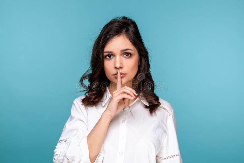 保持沈默被隔绝的英俊的女孩陈列在蓝色背景 免版税图库摄影