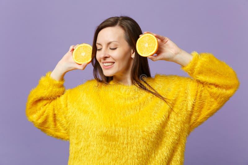 保持眼睛的毛皮毛线衣的美丽的年轻女人闭上拿着在紫罗兰色柔和的淡色彩隔绝的新鲜的成熟橙色果子halfs  免版税库存照片
