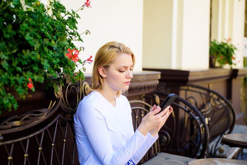 保持联系 妇女镇静面孔短信的智能手机咖啡馆大阳台都市背景 夫人短信的消息朋友白色花费 库存图片