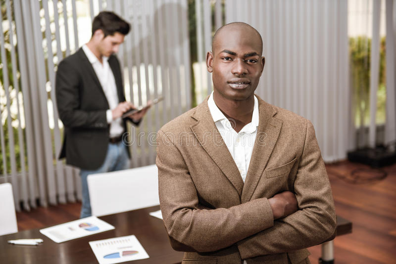 保持胳膊的formalwear的快乐的年轻非洲人横渡 库存照片