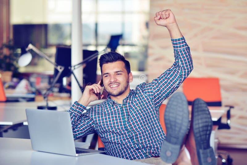 保持胳膊被举和看愉快,当坐书桌的便衣的快乐的年轻人在办公室时 免版税图库摄影