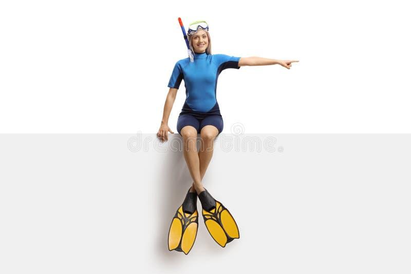 保温潜水服、坐横幅和指向边的一个潜水的面具和鸭脚板的年轻白肤金发的女性 免版税库存图片