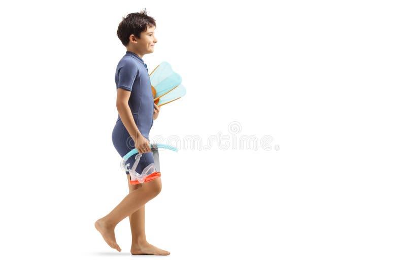 保温潜水服的男孩走和拿着一个潜水的面具和鸭脚板的 库存照片