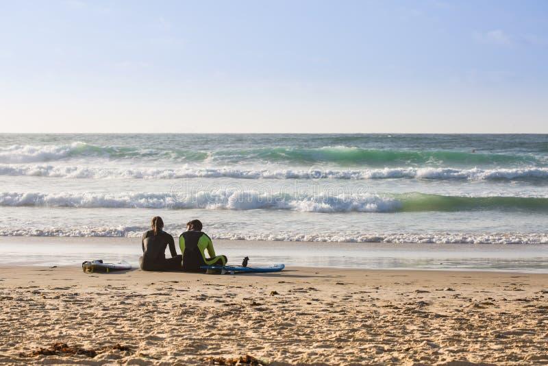 保温潜水服的两位冲浪者坐沙子 免版税库存照片