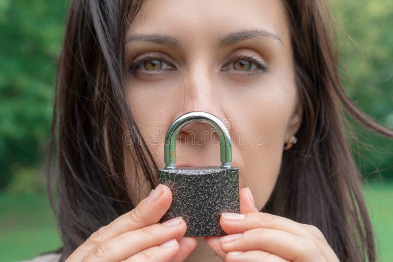 保留与锁的妇女的概念性画象沈默在她的嘴 白种人妇女保持嘴被锁 语言障碍 免版税库存图片