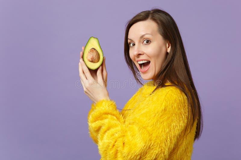 保留嘴开放举行的一半新鲜的成熟绿色鲕梨的毛皮毛线衣的快乐的年轻女人隔绝在紫罗兰 免版税库存照片