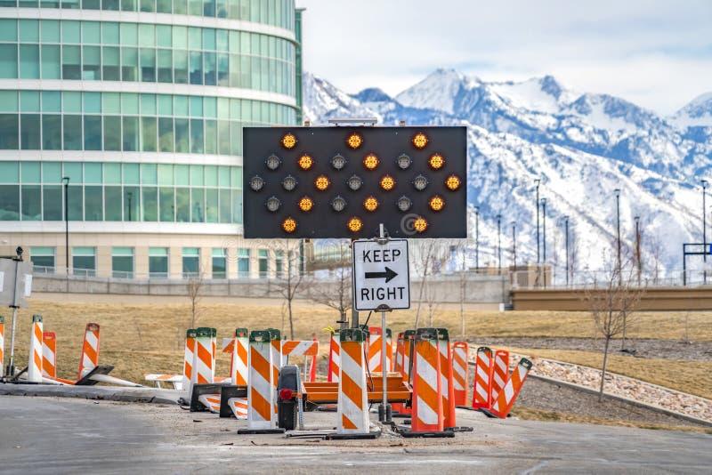 保留在公路安全杆围拢的箭头板下的正确的标志 免版税库存图片