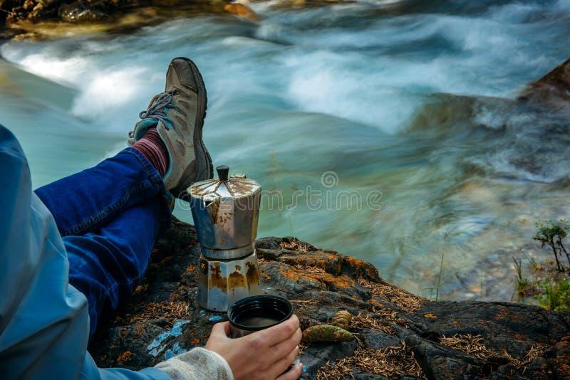 保留在被弄脏的河背景的无法认出的徒步旅行者一个金属杯子  喷泉咖啡壶在石岸站立 免版税库存图片