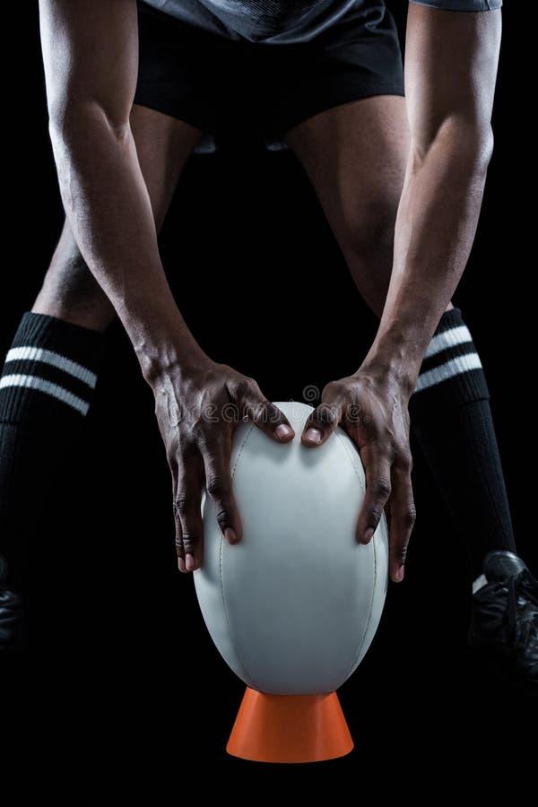 保留在踢的橄榄球球员的中间部分发球区域的球 免版税库存图片