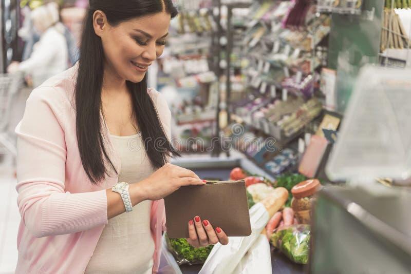 保留小囊的愉快的微笑的妇女在商店 库存图片