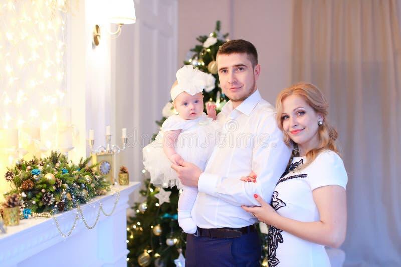 保留小女性婴孩的年轻父母在圣诞树附近在背景 图库摄影
