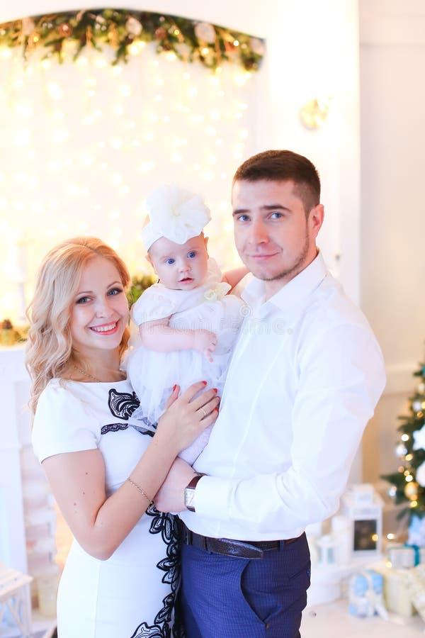 保留小女性婴孩的微笑的母亲和父亲在圣诞节的装饰的室 免版税库存照片