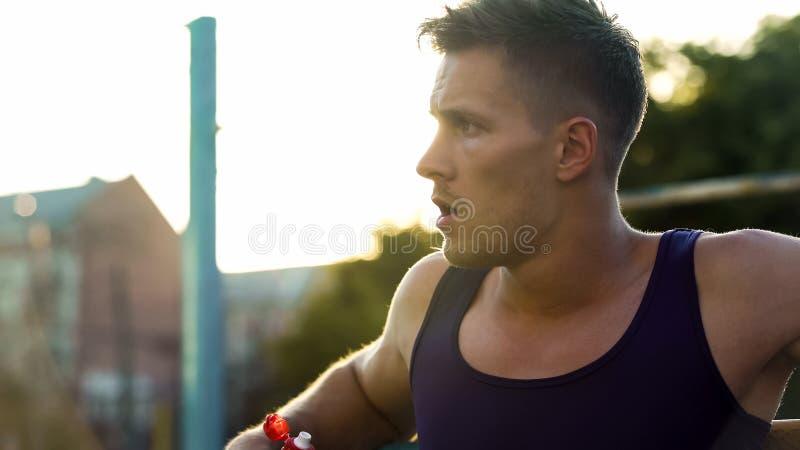 保留水分平衡的英俊的运动员在密集的室外锻炼,体育以后 库存照片