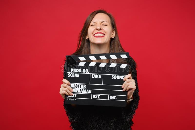 保留眼睛的黑毛皮毛线衣的俏丽的微笑的女孩关闭了,对经典黑电影制作clapperboard负被隔绝  库存图片