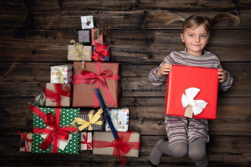 保留礼物的homewear的愉快的微笑的儿童女孩在与圣诞树杉木的垂直的顶视图葡萄酒木头被做  免版税库存照片