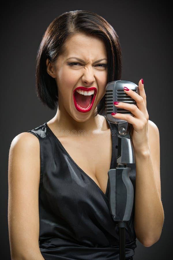保留话筒的呼喊的女性音乐家 免版税图库摄影