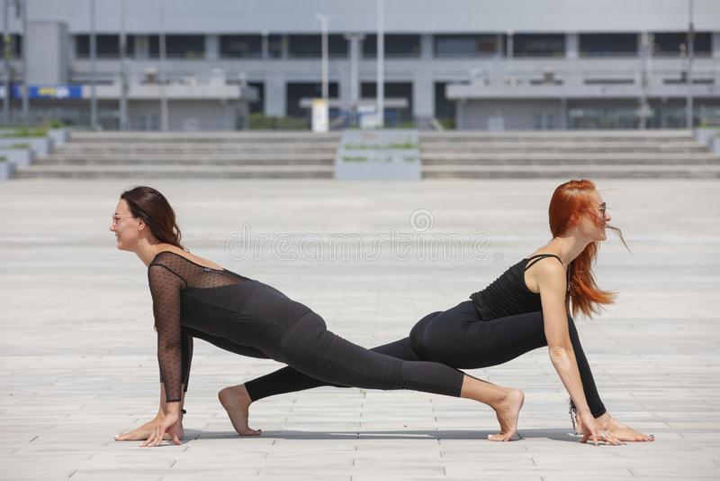 保留适合的两名成熟妇女通过做瑜伽在夏天 免版税库存照片