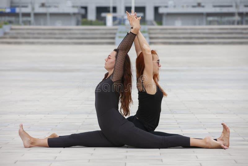 保留适合的两名成熟妇女通过做瑜伽在夏天 库存照片