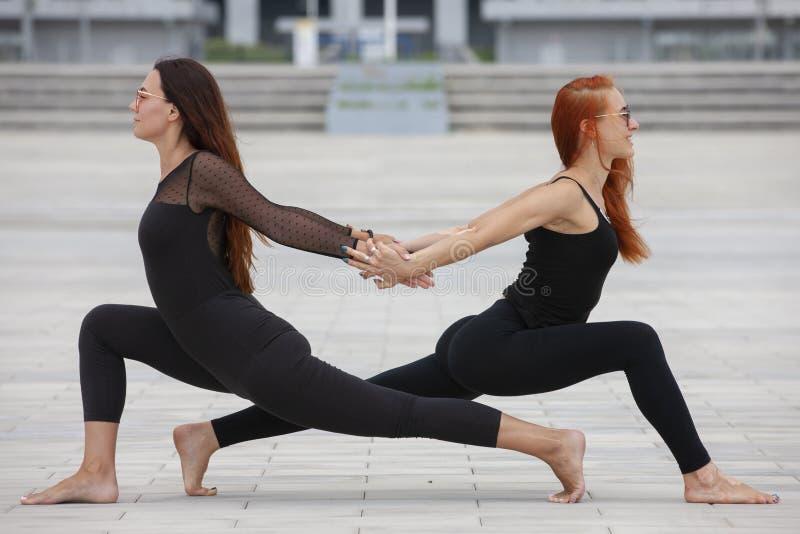 保留适合的两名成熟妇女通过做瑜伽在夏天 库存图片