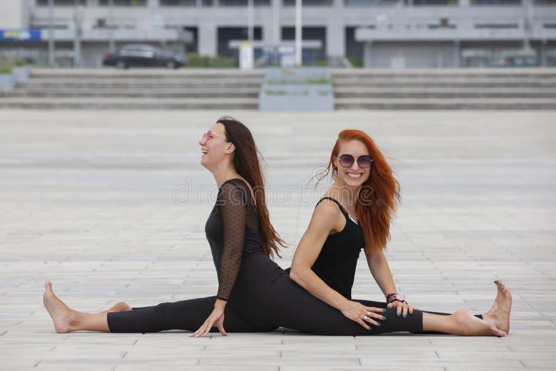 保留适合的两名成熟妇女通过做瑜伽在夏天 免版税库存图片